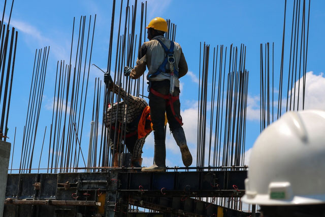 construction workers standing on top of steel frames